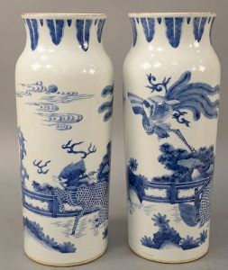 Pair of blue and white sleeve form porcelain vases, 19th century or older, landscape scene with flying phoenix on qilin. height 15 1/2 inches.