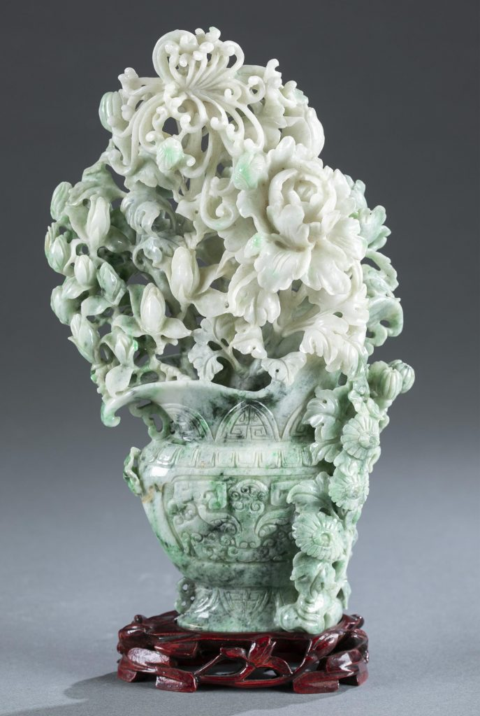 Large Chinese jade carving of flower arrangement in a flattened double-handle vase decorated with taotie masks. Approximately 10½in. Accompanied by wooden base. Provenance: Collection of Anna Chennault. Estimate: $600-$900