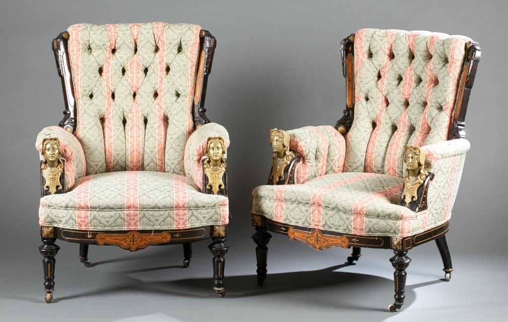 Pair of 19th-century armchairs, Egyptian Revival style, attributed to Pottier & Stymus, tufted upholstered backs flanked by carved stiles; cast bronze busts at the end of each arm. Estimate: $1,500-$2,500
