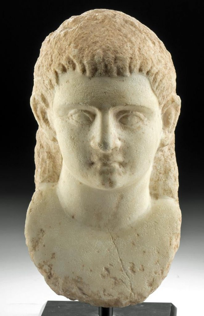 Finely carved Greek Hellenistic marble bust of a youth, 3rd to 1st century BCE, 11in high (inclusive of stand), book example, formerly in a private Paris collection. Estimate $22,000-$30,000