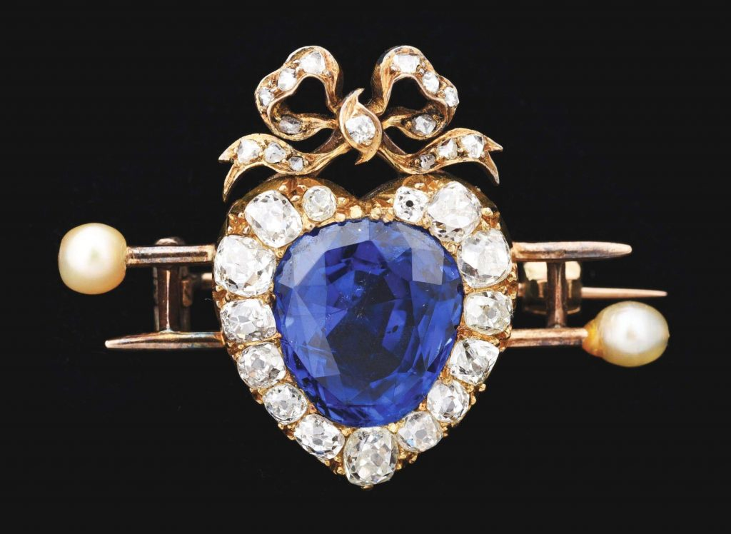Victorian heart-shape brooch featuring natural blue pear-shape sapphire, approximate weight 5.52 carats, framed by 15 mixed old mine-cut cushion diamonds, topped with a bow set with 15 smaller diamonds. Accompanied by original AGL Colored Stone Certificate. Estimate $60,000-$120,000