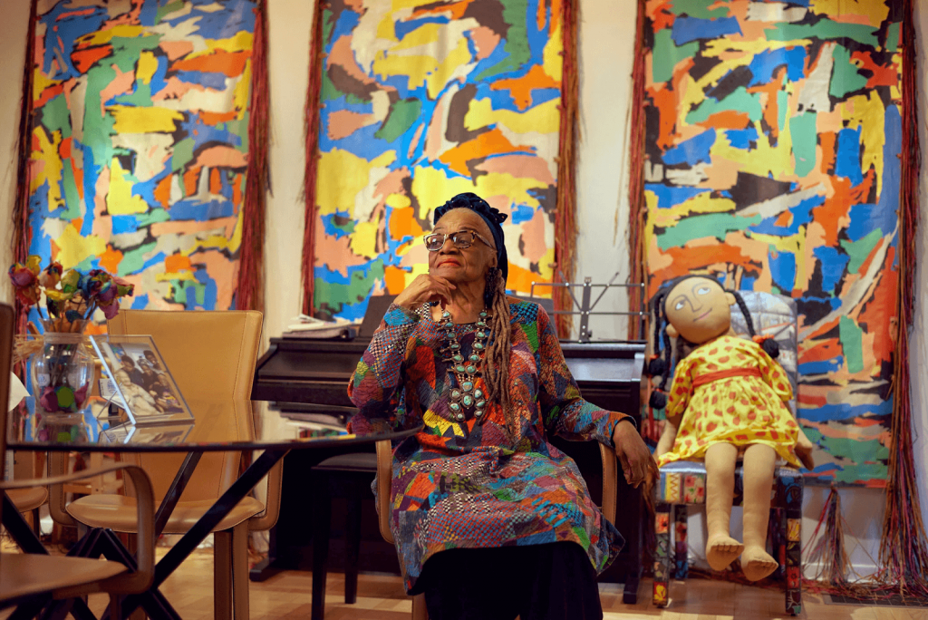 Faith Ringgold in front of California Dah #3, 1983 in her home. Image from The New York Times.