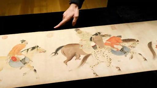Sotheby's staff member pointing out details in Ren Renfa's Five Drunken Princes Returning on Horseback. Photo from Reuters.