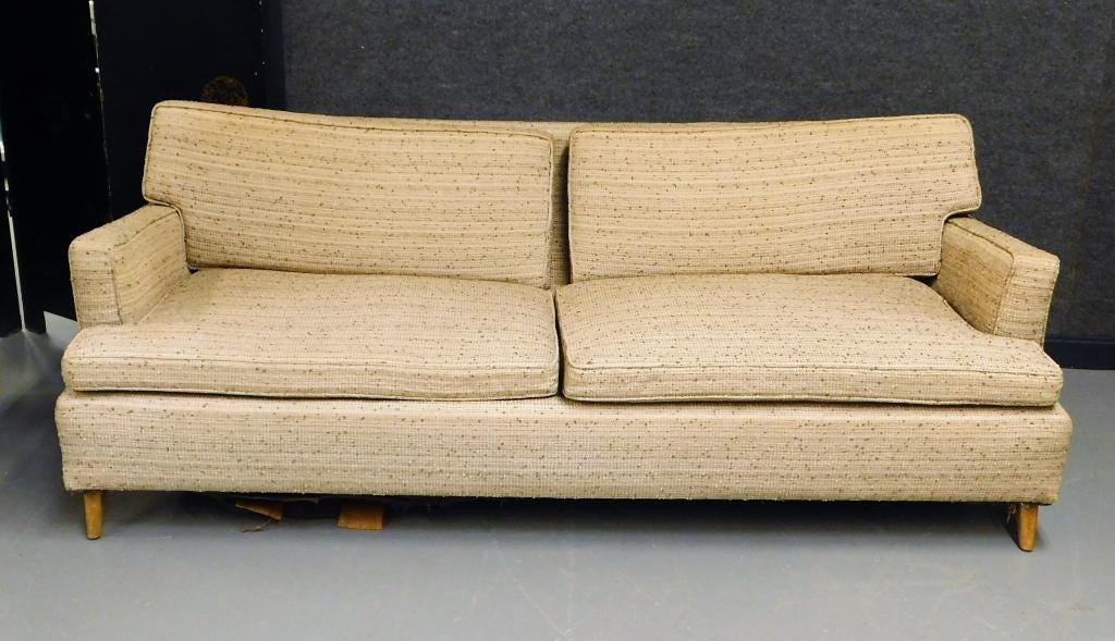 Cream tweed upholstered fabric couch by Paul McCobb (Mass., 1917-1969) for Custom Crafts, Inc., supported by a wood base and measuring 76 inches in width (est. $100-$200).
