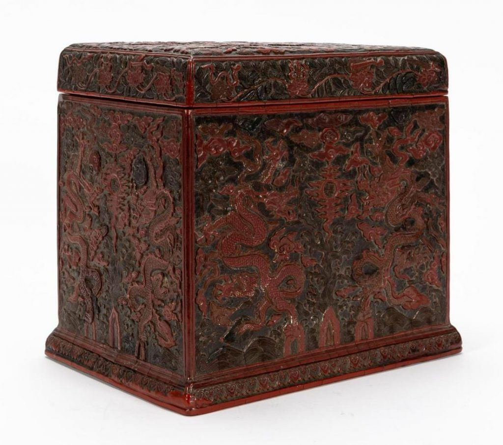 Chinese Ming Dynasty (1368-1644) carved cinnabar lidded box, 11 ¾ inches by 13 inches, showing a dragon chasing the flaming pearl and a character mark to the pearl on lid ($81,250).