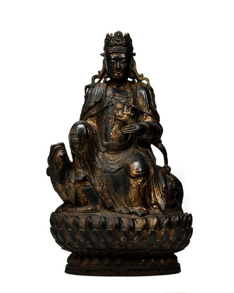 Sino-Tibetan bronze figure of a Guan Yin seated in rajalilasana and wearing heavy robes, jewelry and a pierced crown; 450mm high x 270mm wide. Weight: 11kg (24lbs 4 oz). Estimate: £2,000-£3,000