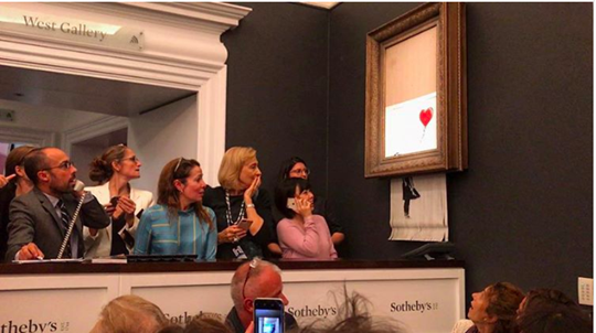 Onlookers stunned as Banksy's Girl With a Balloon self-destructs at Sotheby's. Image from Artnet.