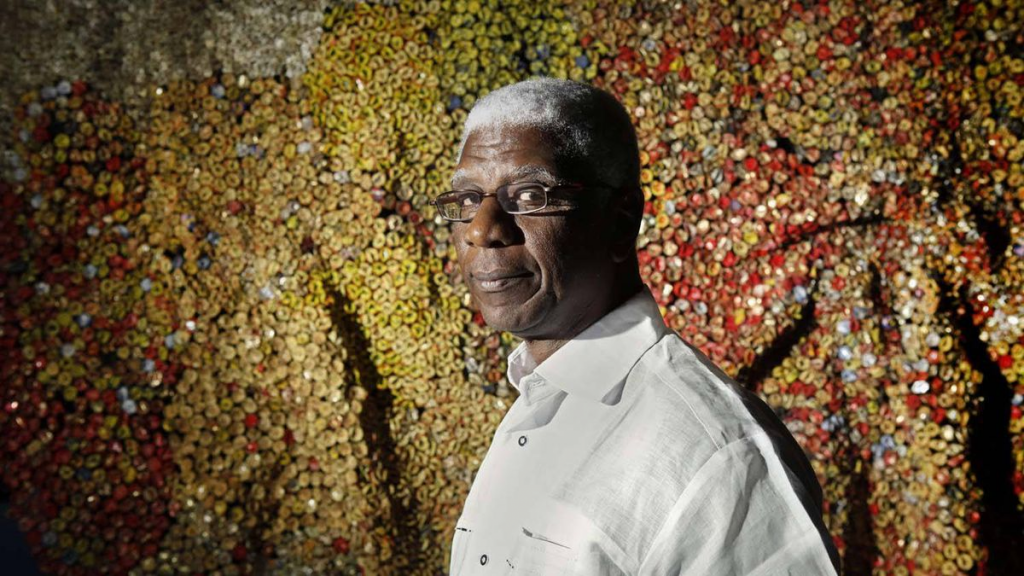 El Anatsui with one of his works at the Royal Ontario Museum. Image courtesy of Moe Doiron/ The Globe and Mail.