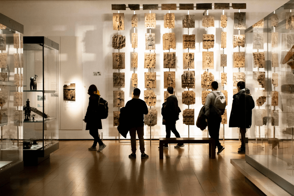 British Museum visitors view a display of Benin Bronzes. Image by Lauren Fleishman for The New York Times.