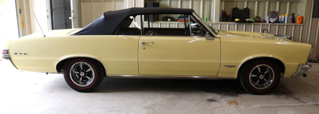 Yellow 1965 Pontiac GTO classic car in excellent condition inside and out (est. $35,000-$50,000).