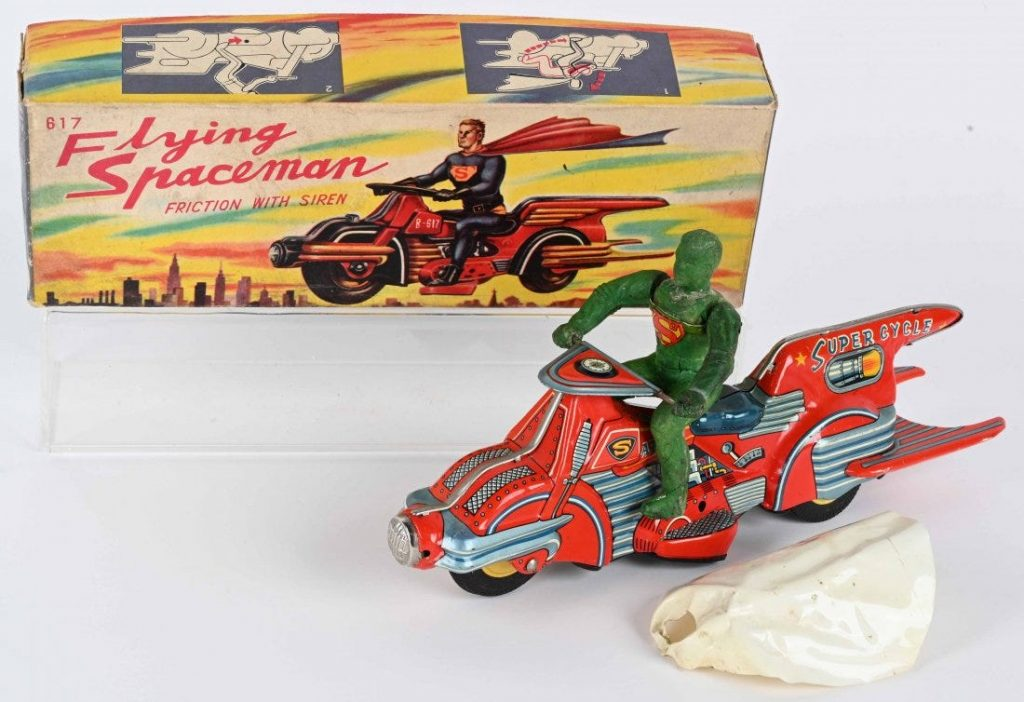 """Bandai (Japan) friction-powered 'Flying Spaceman' on 'Super Cycle' with original caped, green rubber """"Superman"""" figure. Accompanied by colorfully illustrated box lid. The top lot of the sale, it sold for $55,200 against an estimate of $15,000-$25,000."""