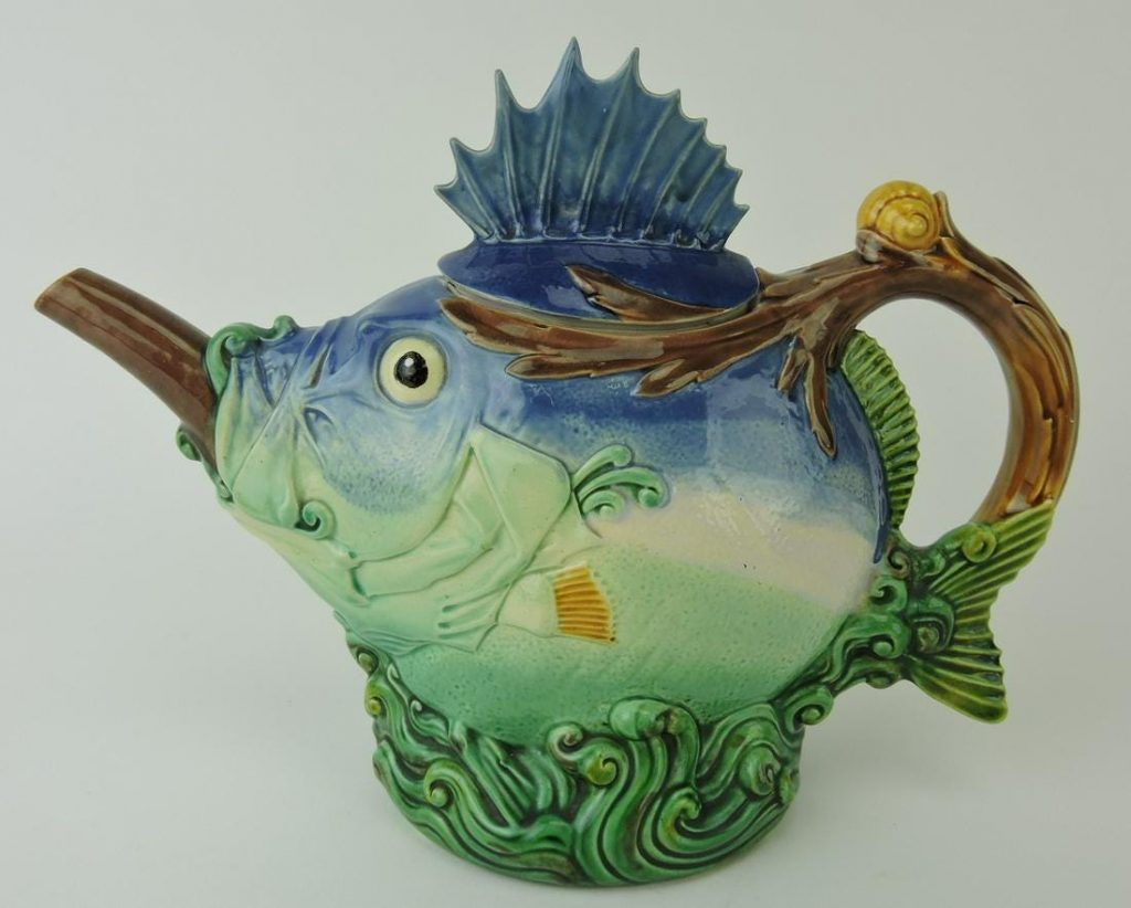 Minton majolica blowfish teapot and cover, modeled as a fantastic fish with brown spout emerging from its mouth, supported on green waves, 7 inches tall (est. $10,000-$15,000).