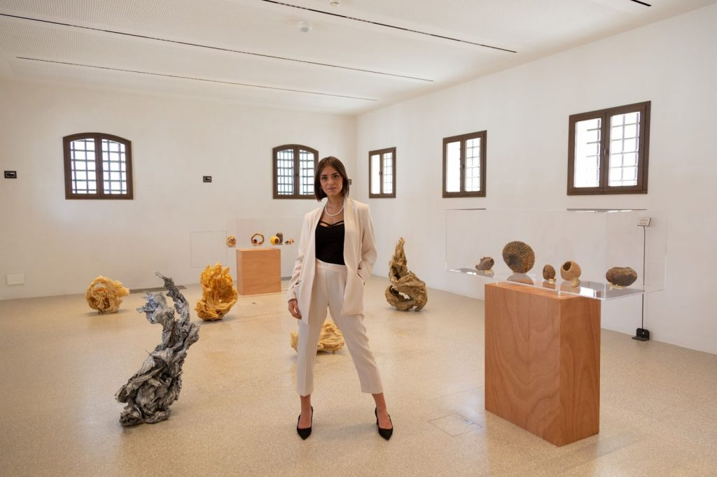 """Elisa Carollo with works by Fabio Roncato and Luca Trevisani at """"Italian Twist"""", an exhibition she co-curated for Fondazione Imago Mundi, Treviso. Image by Marco Pavan."""