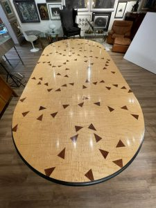 """Dining table designed by Wendell Castle (American, 1932-2018), inlaid with purpleheart triangles and inlaid dots spelling """"The Check's in the Mail"""", the table's title ($70,110)."""