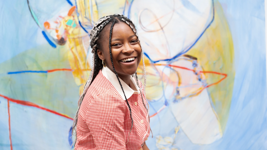 Jadé Fadojutimi with her painting. Image courtesy of the artist and Pippy Houldsworth Gallery, London.