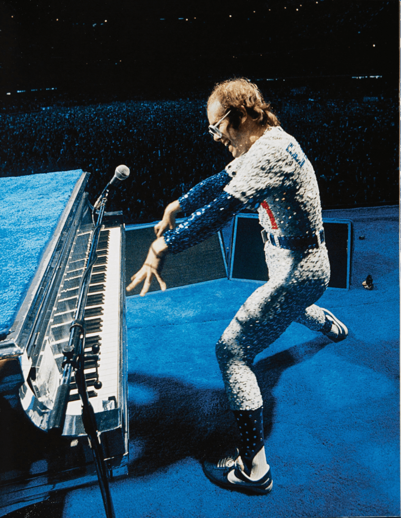 Sir Elton John playing the grand piano at a show. Image from Heritage Auctions.
