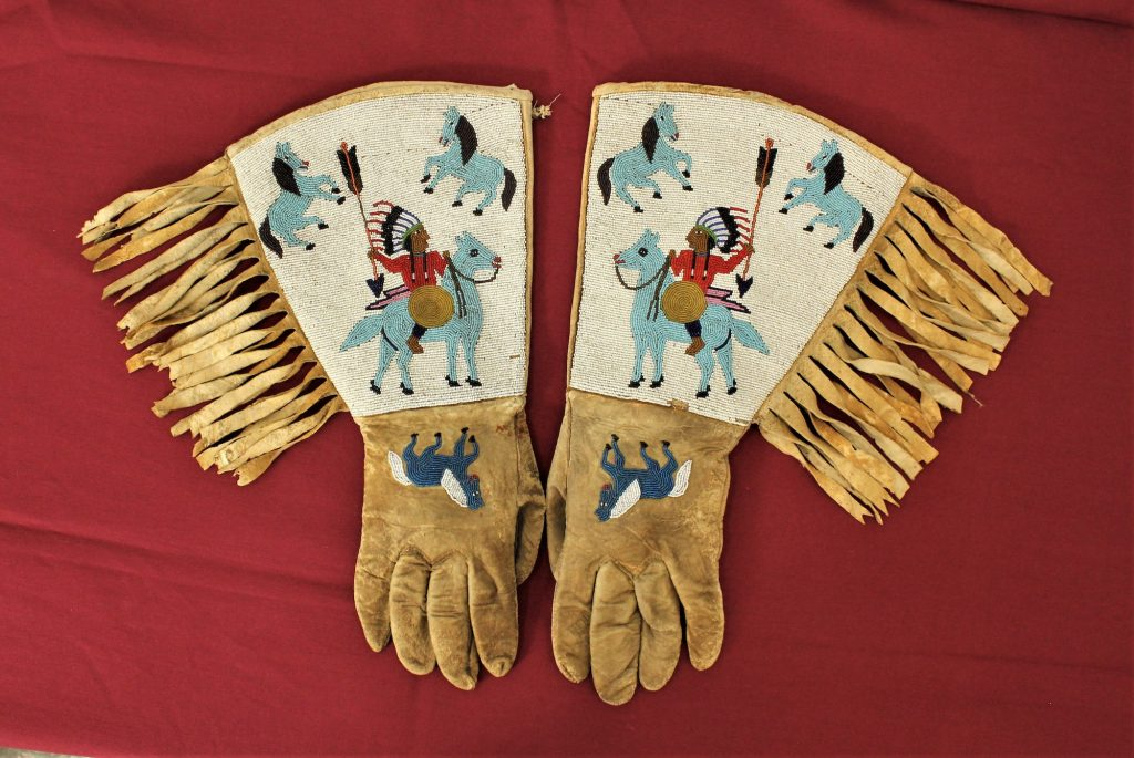 August 28, 2021 auction highlight: Stunning turn-of-the-century Native American (Plateau) gauntlets, fully beaded with images of multiple figures, including Indian chiefs and horses. Cuffs adorned with long fringe. Image courtesy of New Frontier Shows