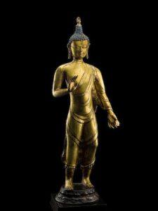 A GILT COPPER ALLOY FIGURE OF STANDING BUDDHA