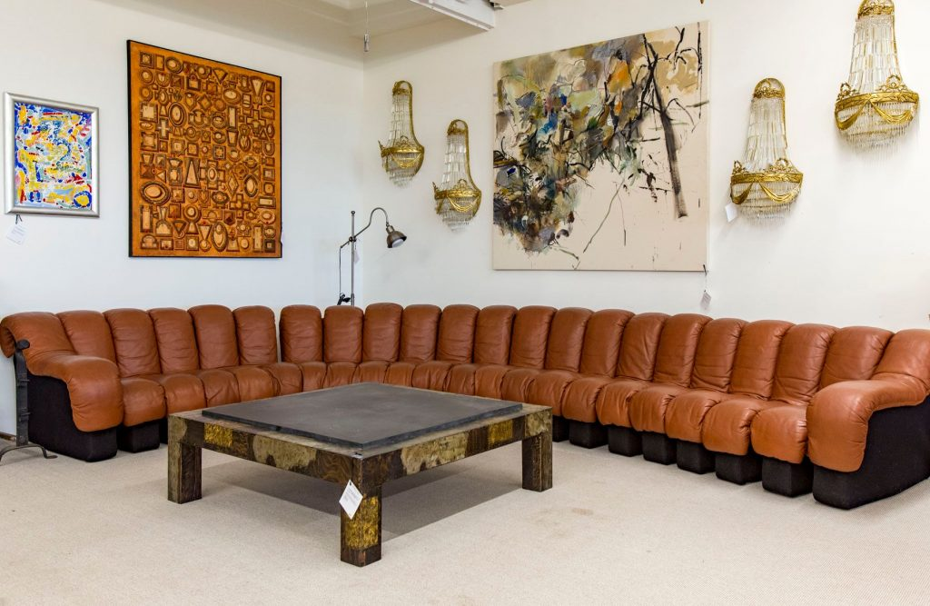 DS-600 sofa by De-Sede wraps around a Paul Evans for Directional coffee table, 1960s. Hollywood Regency style sconces and contemporary art decorate the walls above.