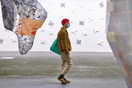 A visitor walks through Art Basel 2021. Image © Art Basel.